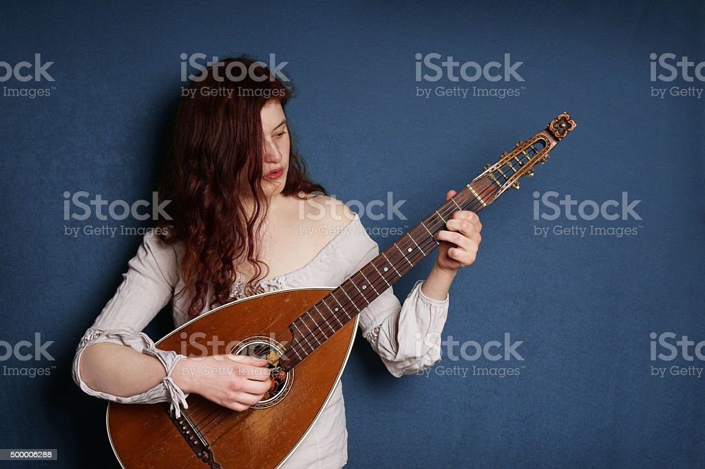 woman playing lute instrument stock photo