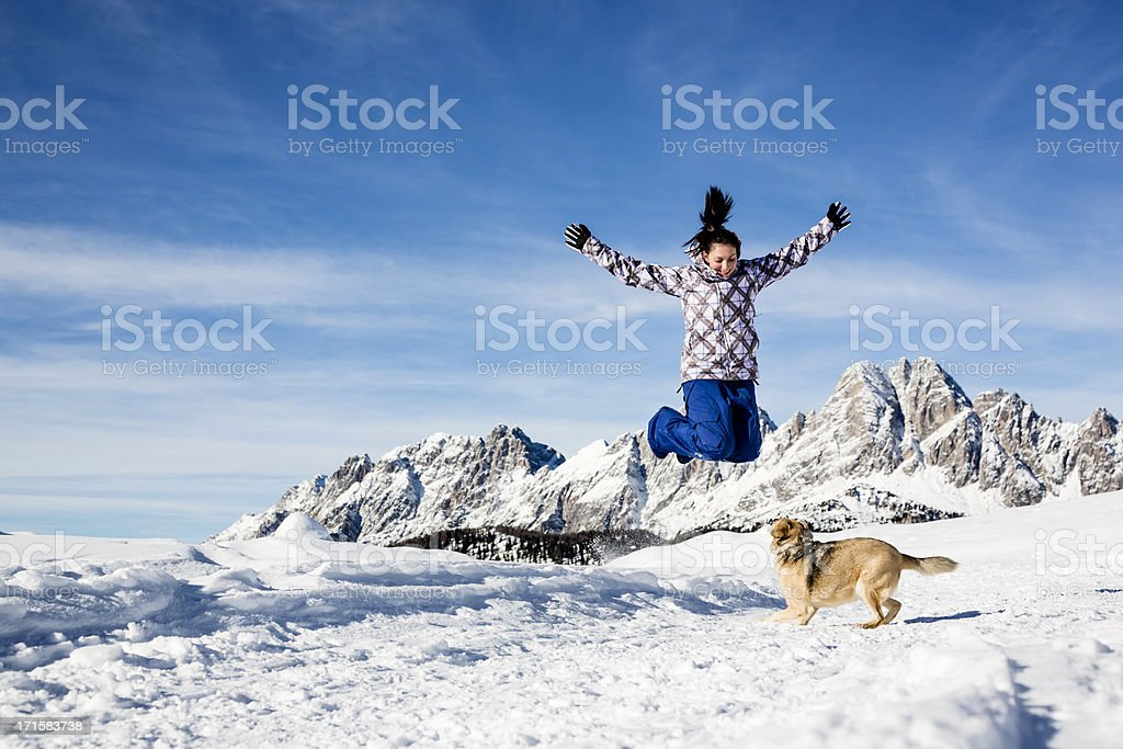 Woman playing on snowy landscape with her dog royalty-free stock photo