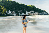 Woman playing on ukulele on the beach