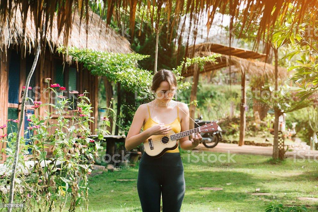 Woman playing on ukulele stock photo