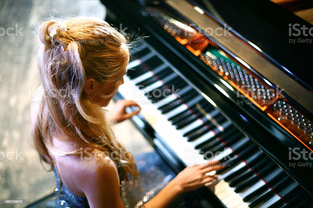 Woman playing piano in a concert. stock photo