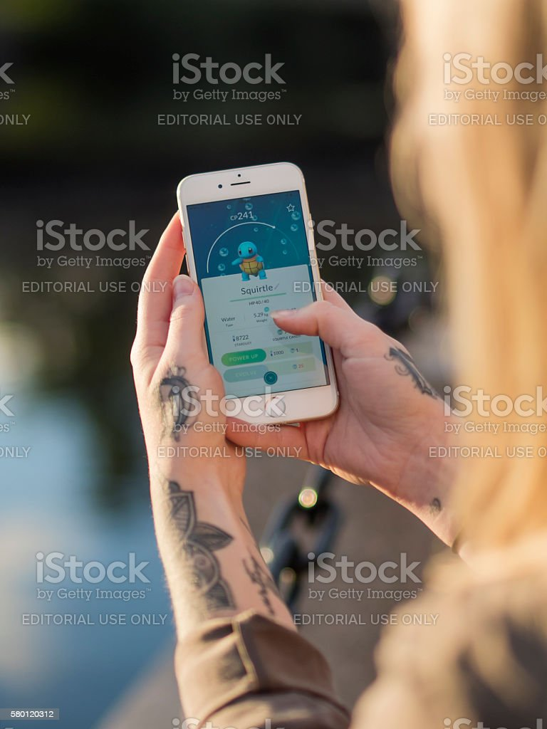 Woman Playing Pokemon GO on a Cellpohne stock photo