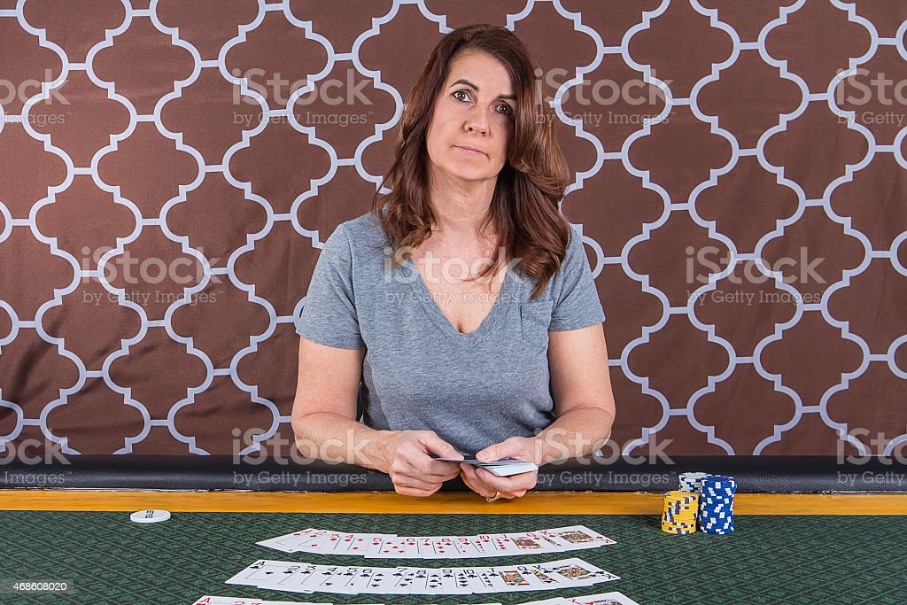 Woman playing poker at a table stock photo