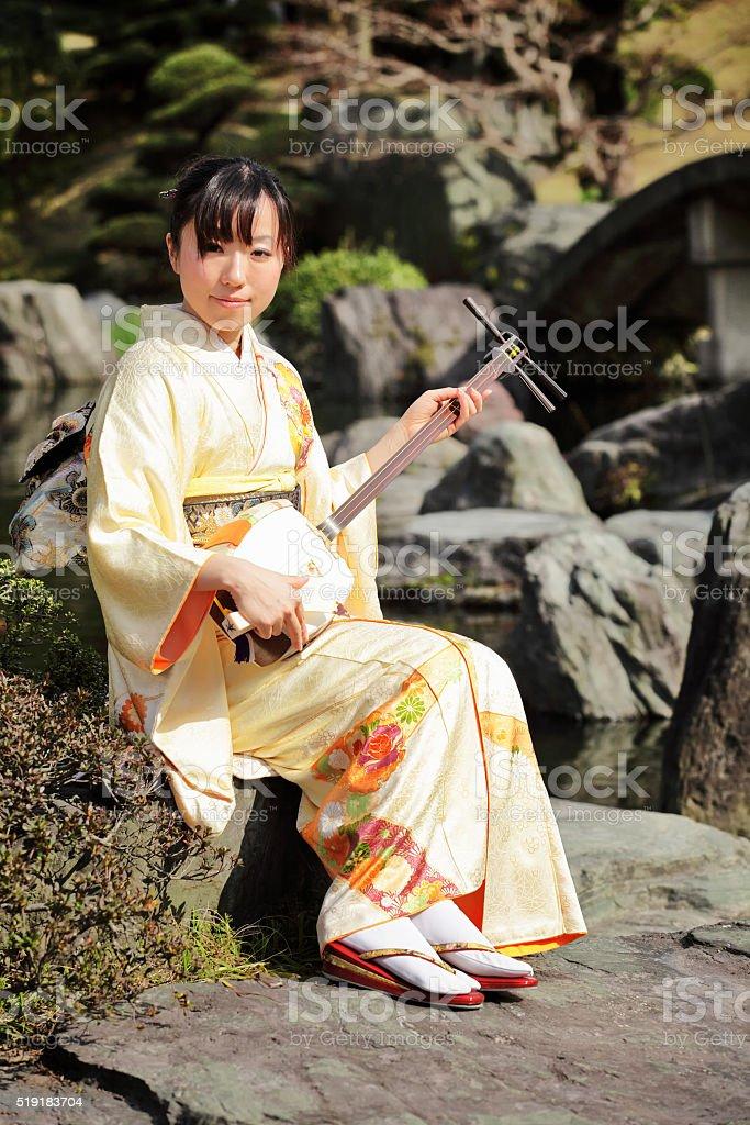 Woman playing shamisen in garden stock photo