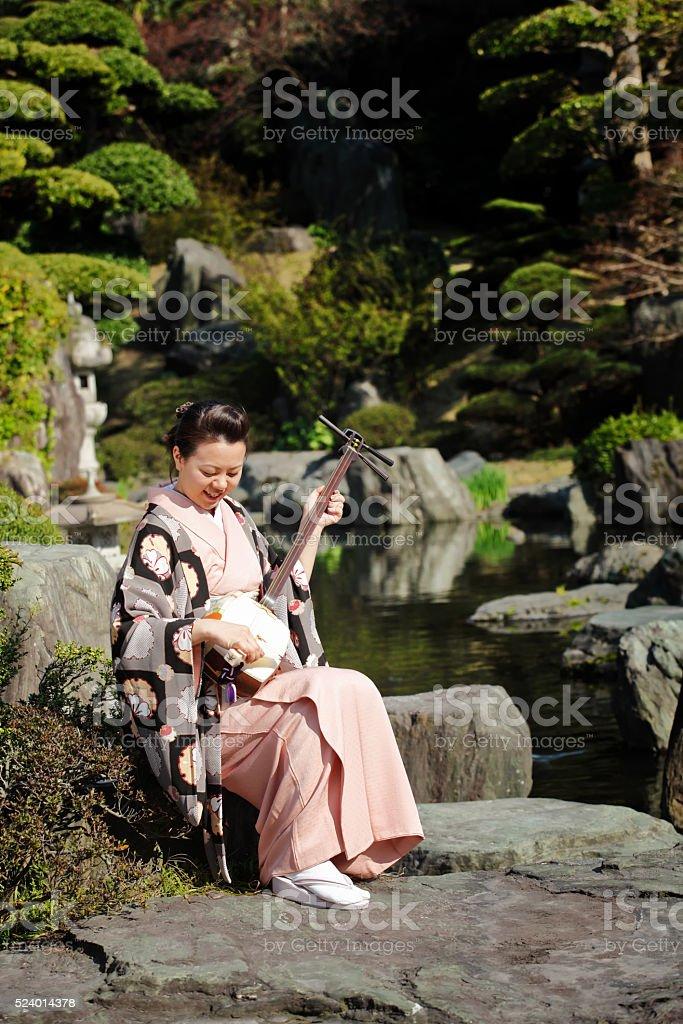 Woman playing shamisen in Japanese garden stock photo
