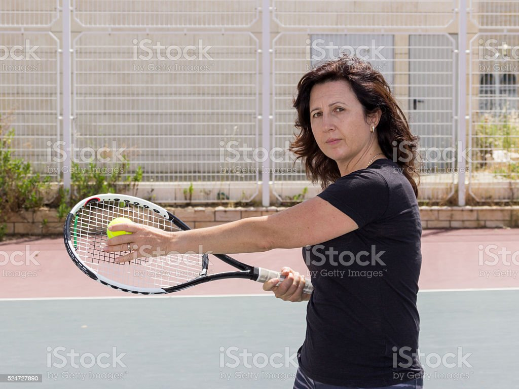Woman playing tennis on the court stock photo