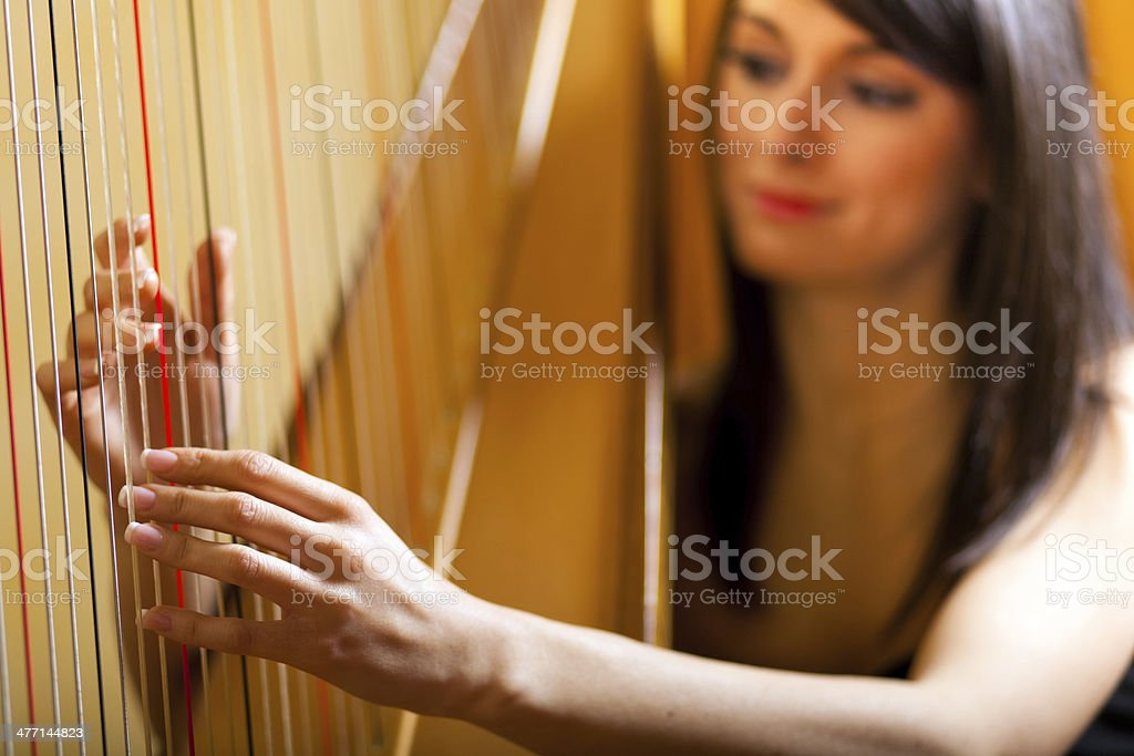 Woman playing the harp stock photo