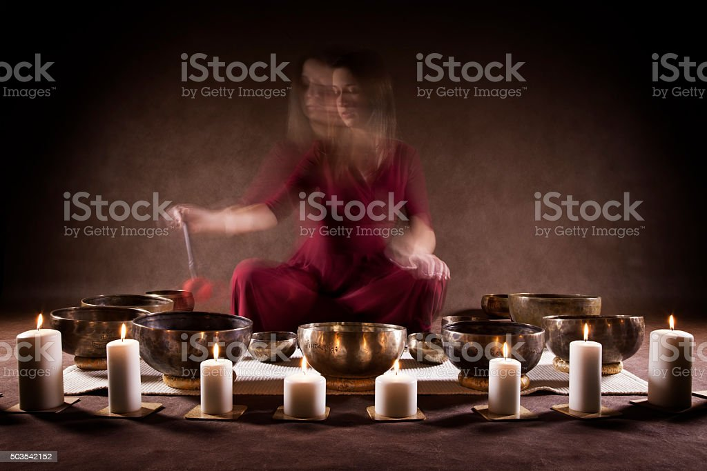 Woman playing Tibetan singing bowls stock photo