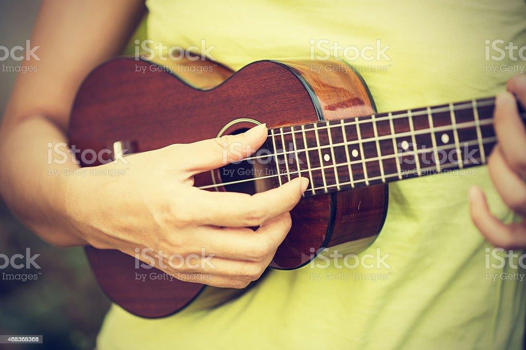 Woman playing ukulele, vintage style. stock photo