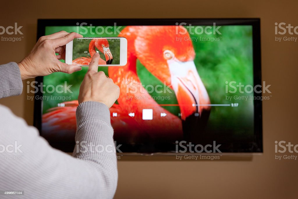 Woman Playing Video From Phone To TV stock photo