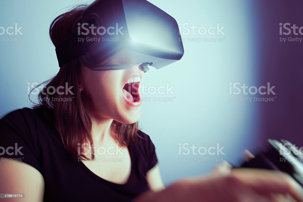 Woman Playing Video Game With Virtual Reality Headset stock photo