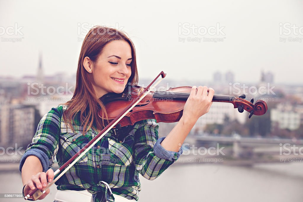 Woman playing violin outdoors stock photo