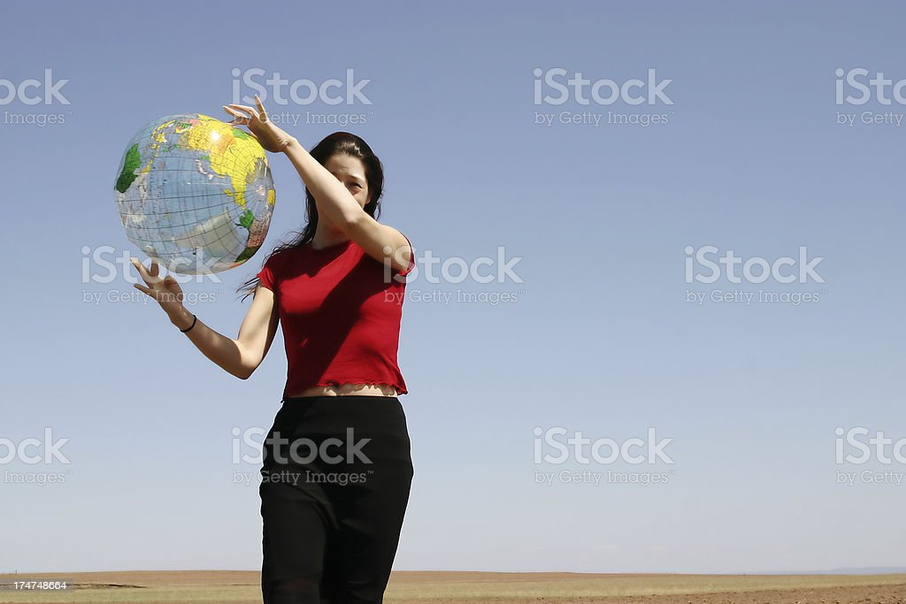 Woman playing with a globe royalty-free stock photo