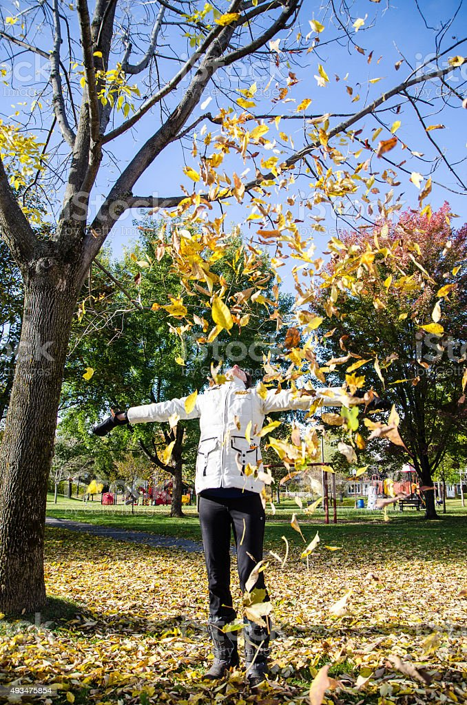 Woman playing with autumn leaves stock photo