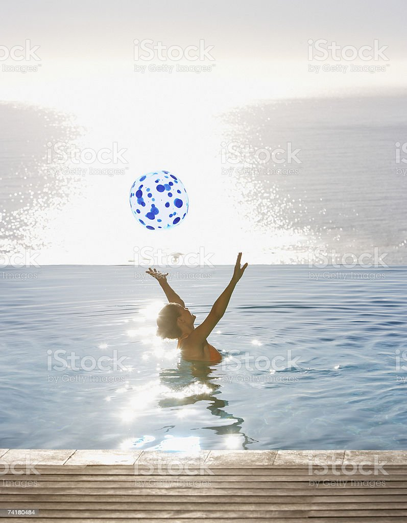 Woman playing with beach ball in infinity pool royalty-free stock photo