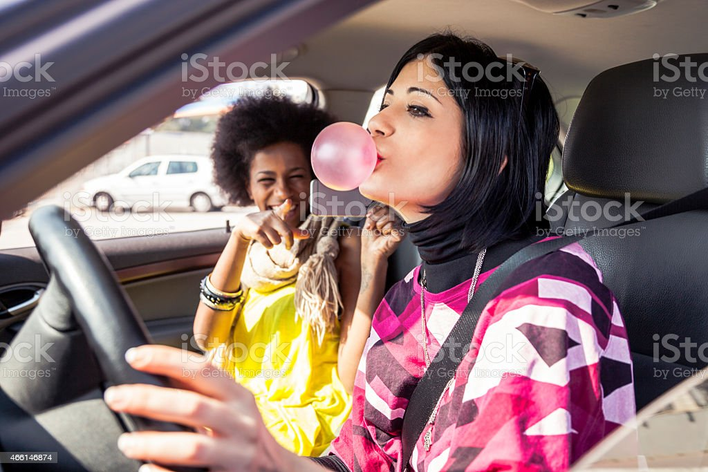 Woman playing with chewing gum on a road trip stock photo