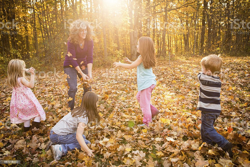 Woman Playing With Children in Beautiful Autumn Woods royalty-free stock photo