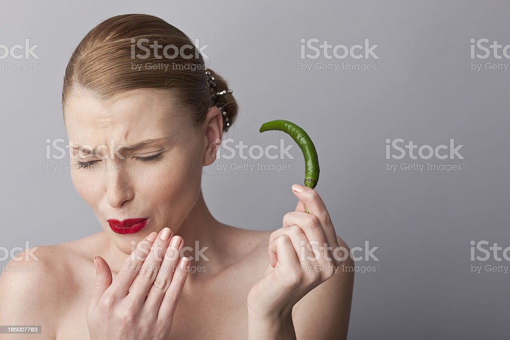 woman playing with green hot pepper stock photo