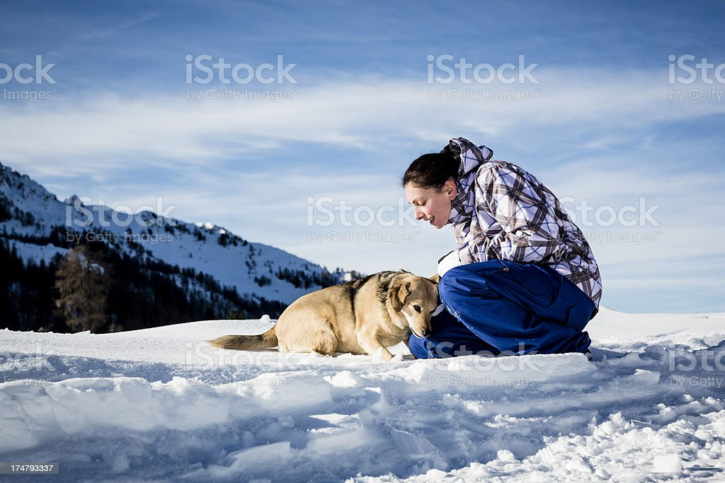 Woman playing with her dog on snowy landscape royalty-free stock photo