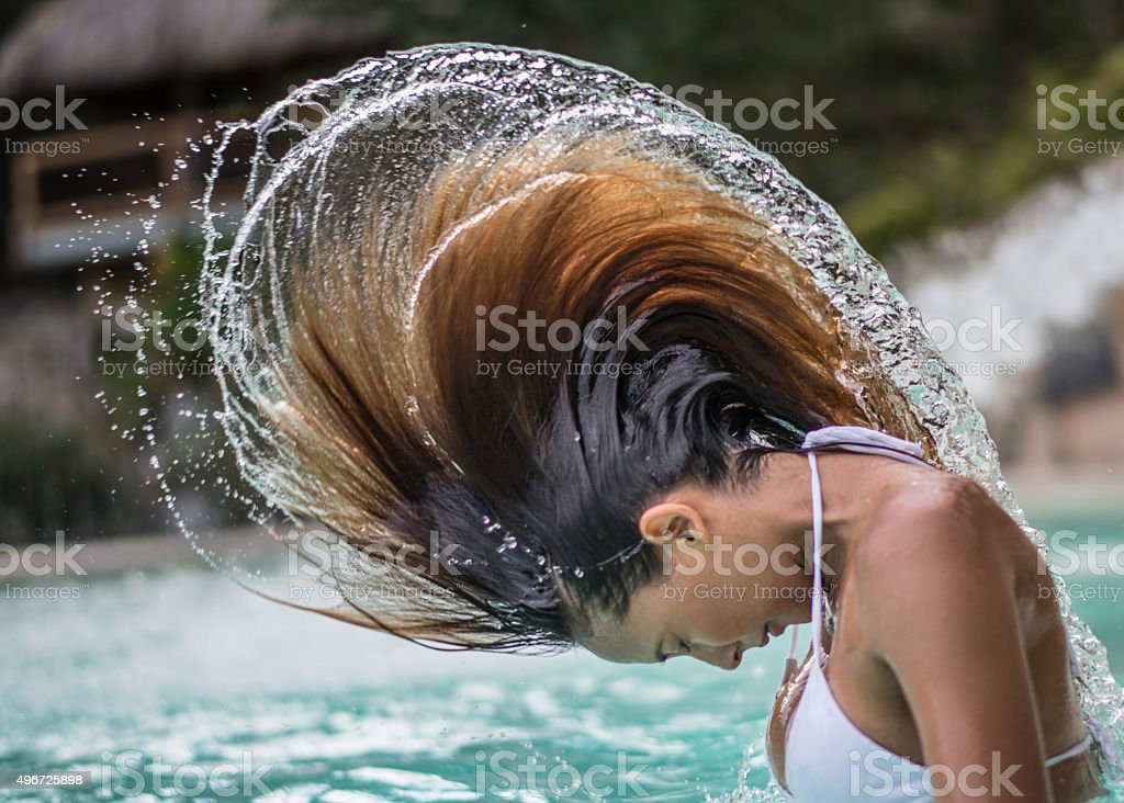 Woman playing with her hair in a swimming pool stock photo