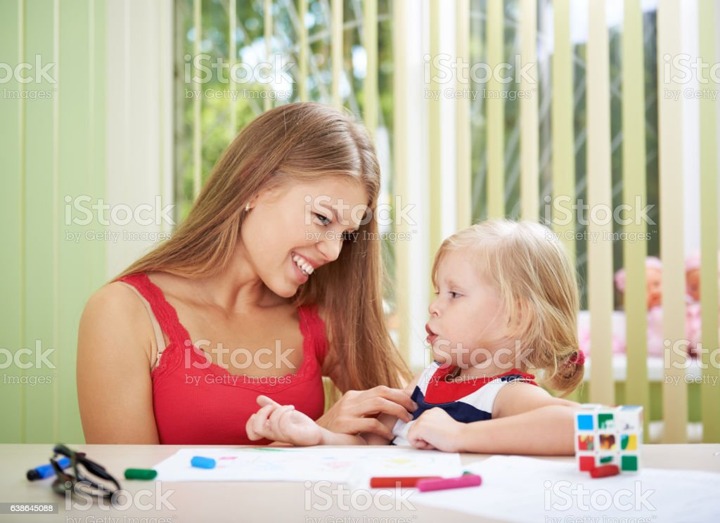 Woman playing with little daughter stock photo