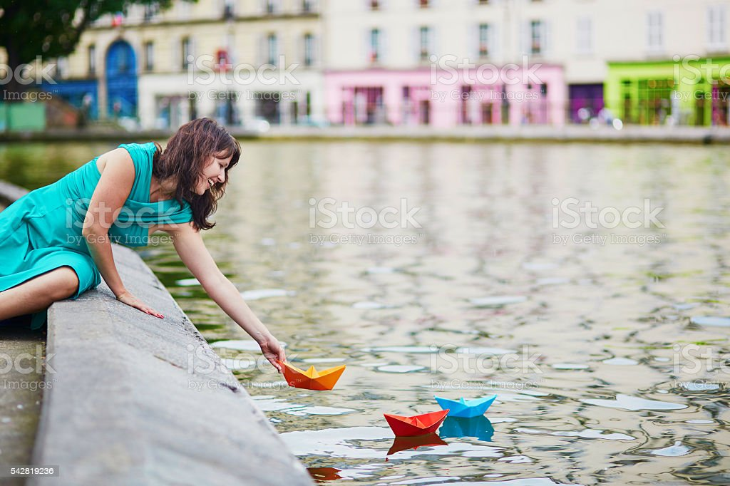 woman playing with paper boats on Canal Saint Martin stock photo