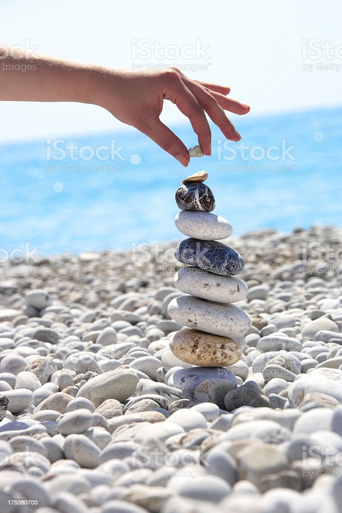 woman playing with ston pile on beach royalty-free stock photo