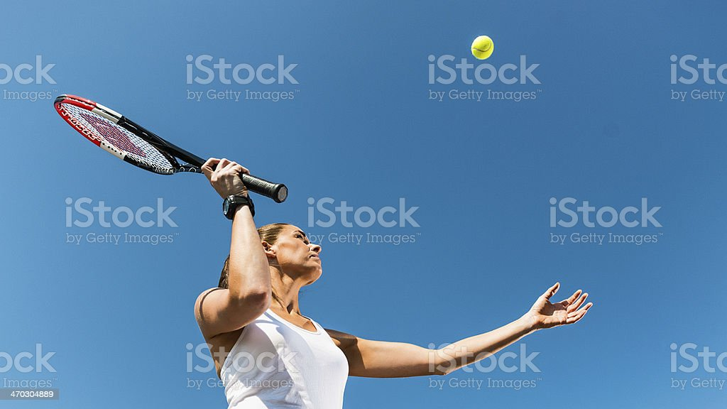 Woman plays tennis on a beautiful summer day royalty-free stock photo