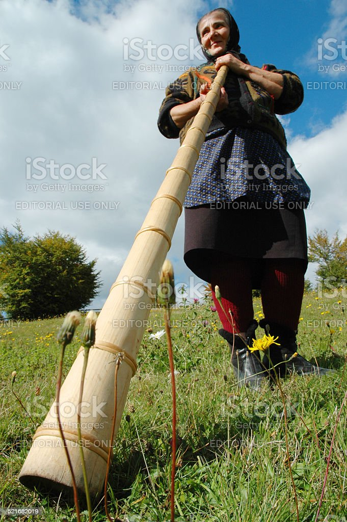 Woman plays the traditional Romanian alpenhorn stock photo