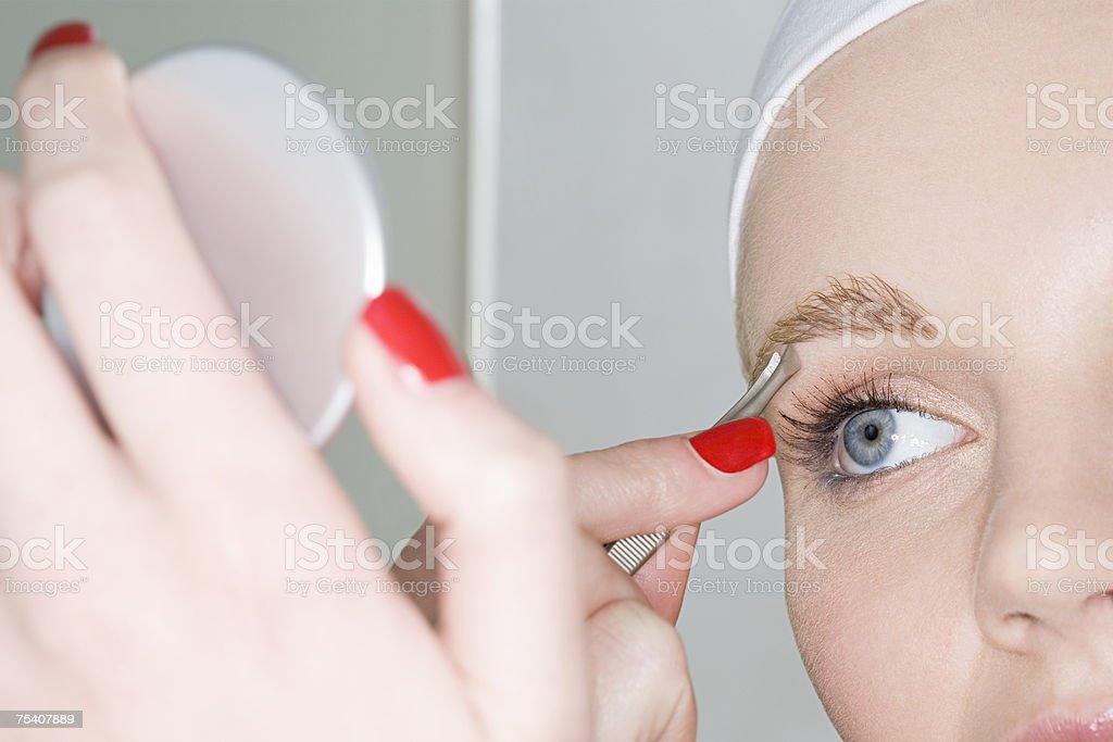 Woman plucking eyebrow stock photo