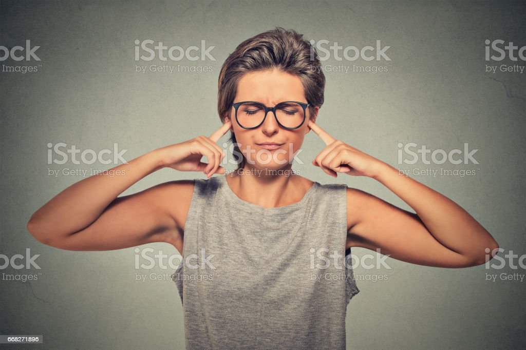 Woman plugging ears with fingers doesn't want to listen eyes closed stock photo