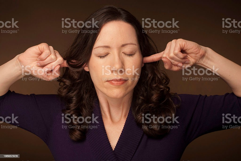 Woman Plugging Her Ears stock photo