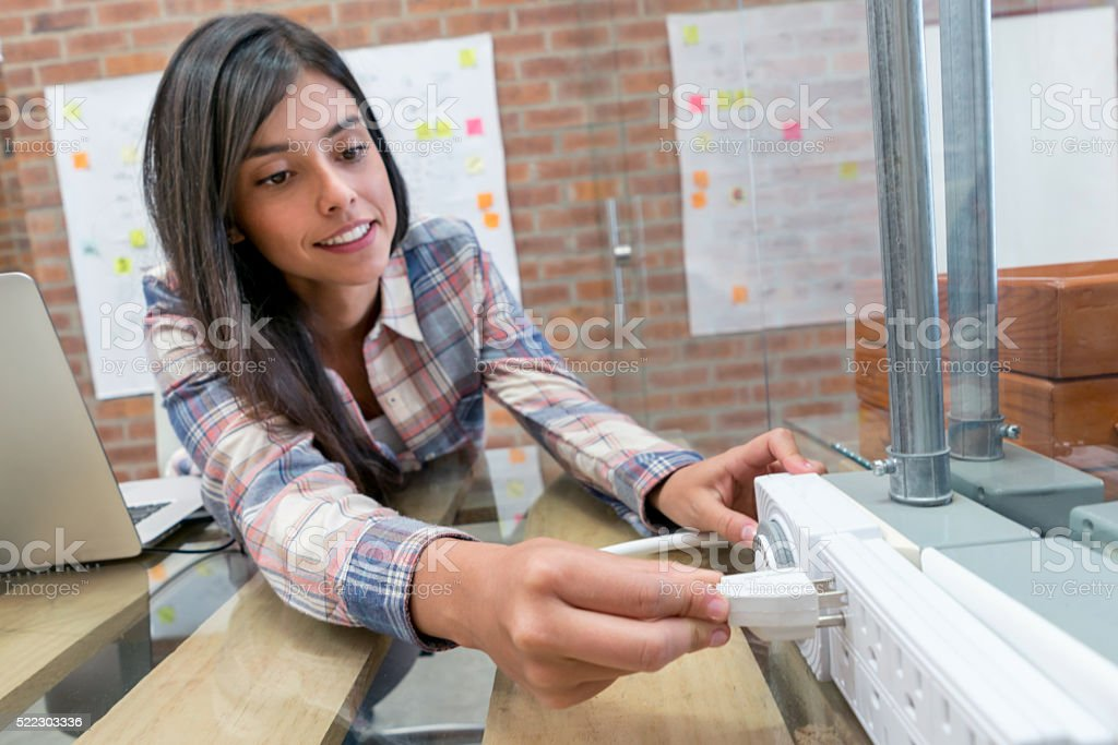 Woman plugging in her laptop at the office stock photo