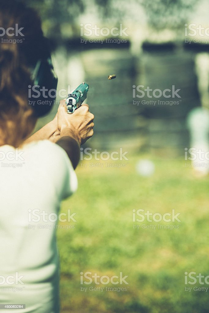 Woman pointing a gun stock photo