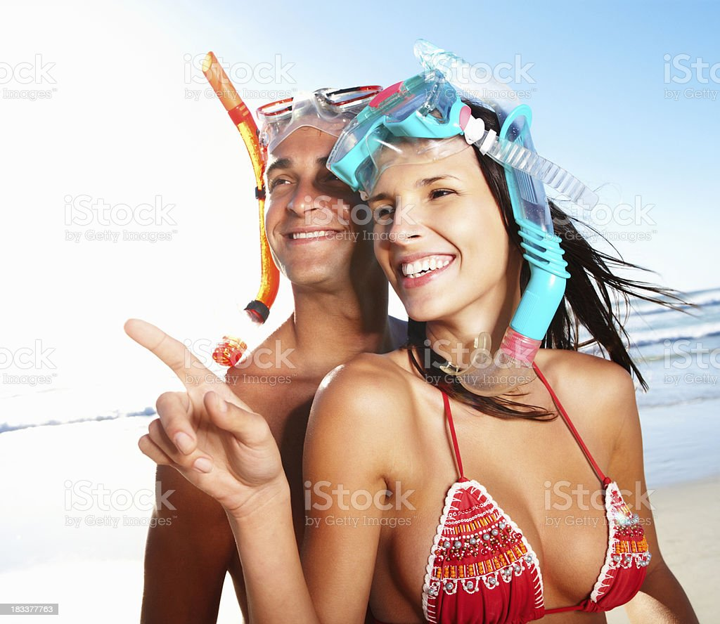 Woman pointing and smiling while wearing snorkel gear royalty-free stock photo