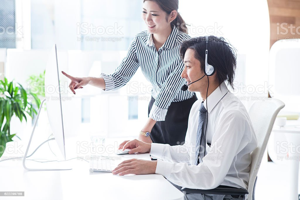Woman pointing at a computer at a call center