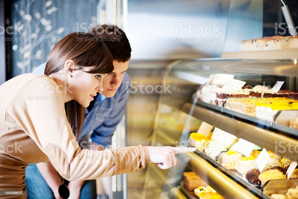 Woman pointing at cakes in display case at confectionery stock photo