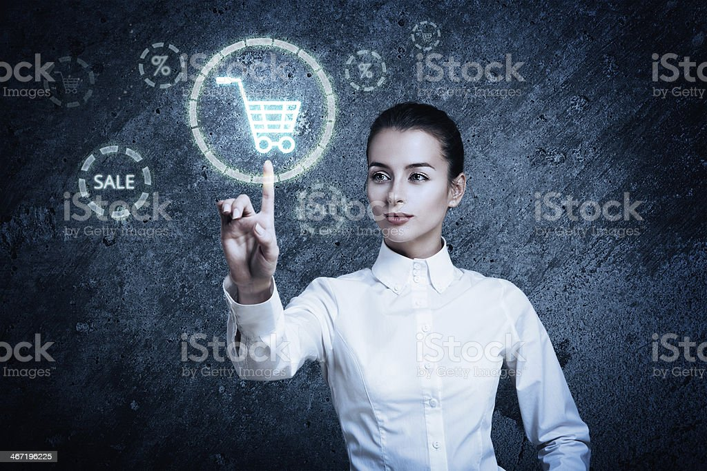 Woman Pointing at Glowing Shopping Cart Icon stock photo