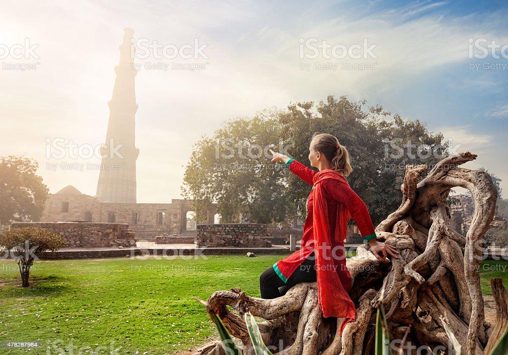 Woman pointing at Qutub Minar stock photo
