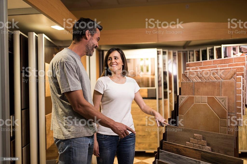 Woman pointing best ceramic floor tile and smiling at man stock photo