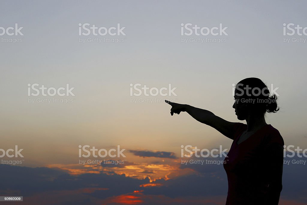 A woman pointing into the distance royalty-free stock photo