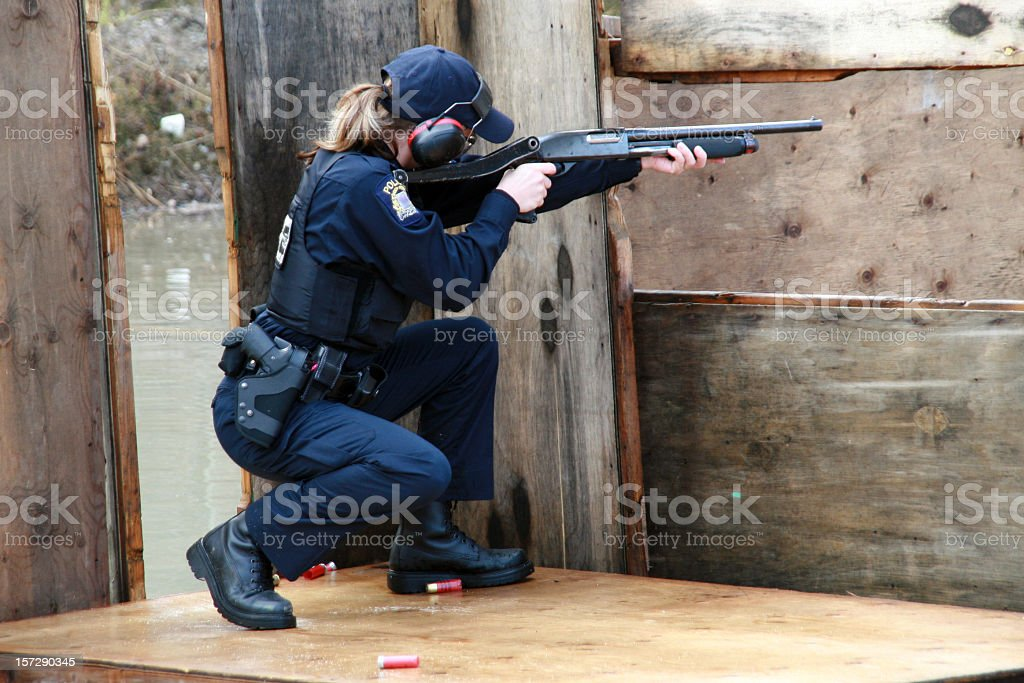 Woman Police Officer Shooting Shotgun at the Practice Field stock photo