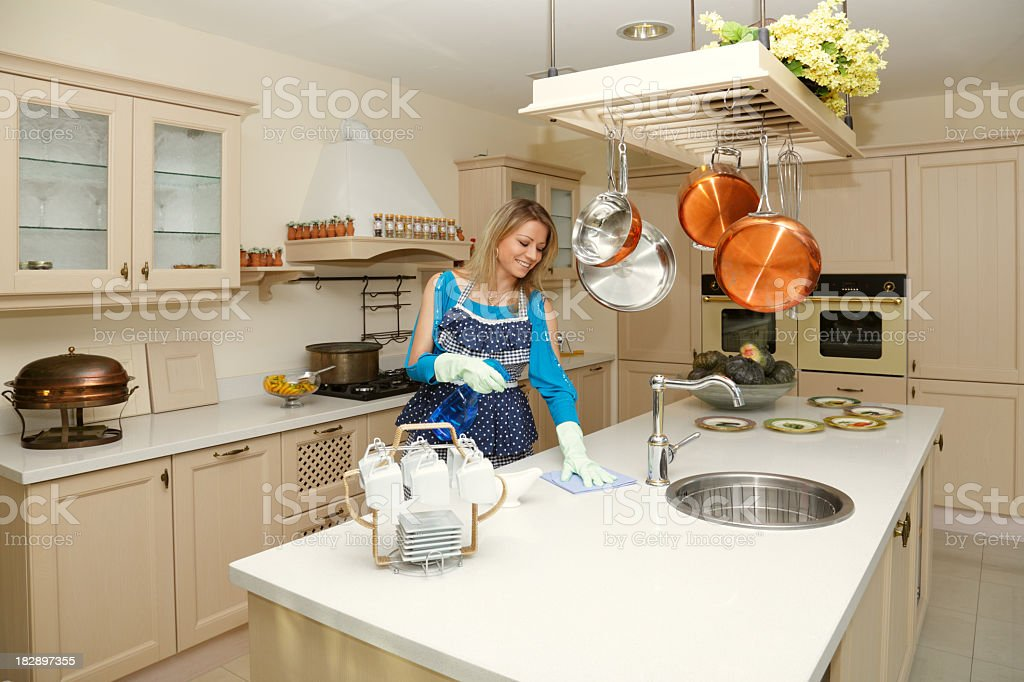 Woman polishes table in the kitchen royalty-free stock photo