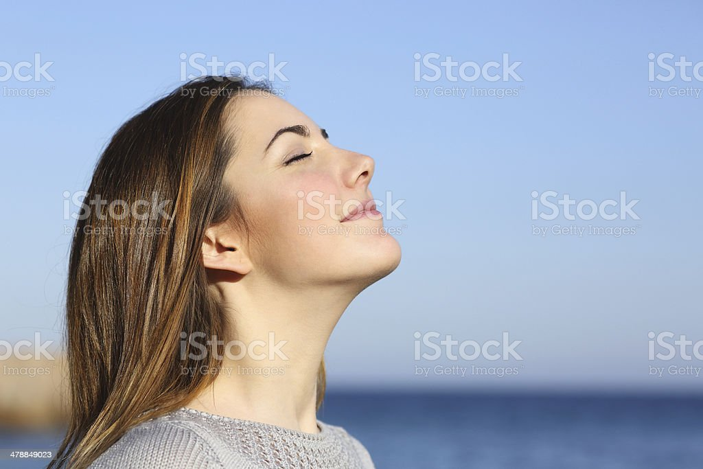 Woman portrait breathing deep fresh air on the beach stock photo