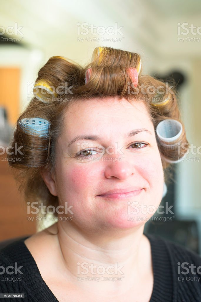 Woman portrait head with hair curlers rollers stock photo