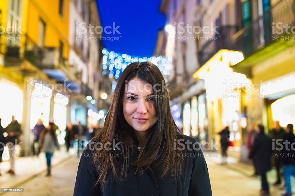 Woman portrait in the illuminated street  with shops stock photo
