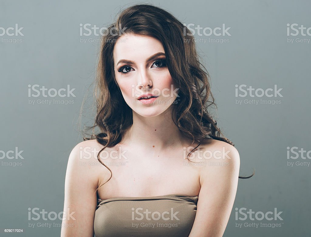 Woman portrait with curly hair on gray background stock photo