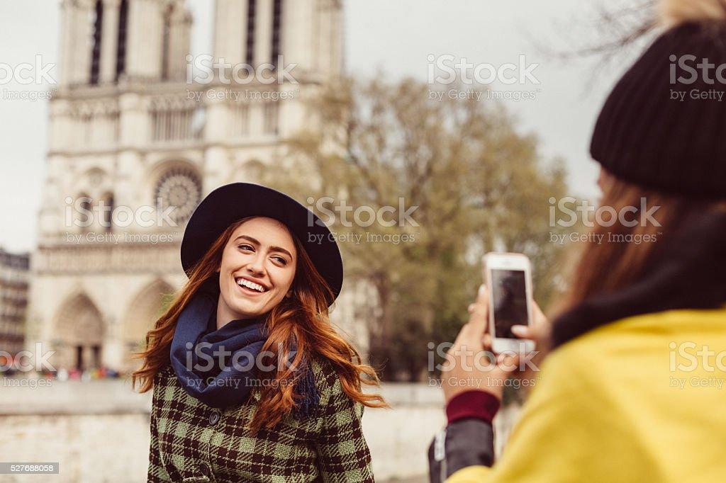 Woman posing for photo against Notre Dame de Paris stock photo
