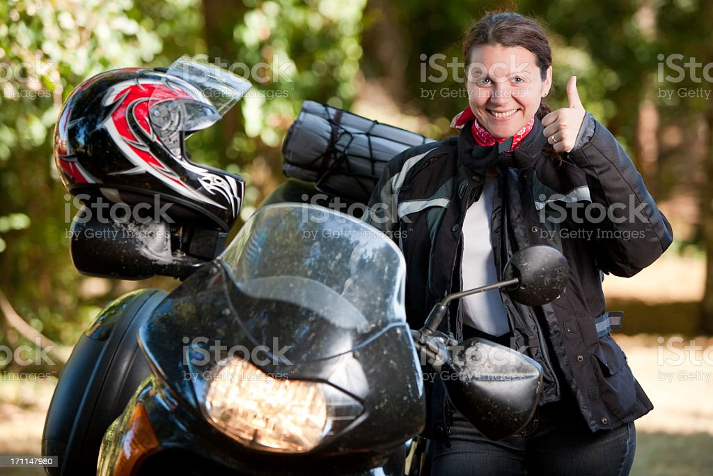 Woman posing happily next to her motorcycle royalty-free stock photo