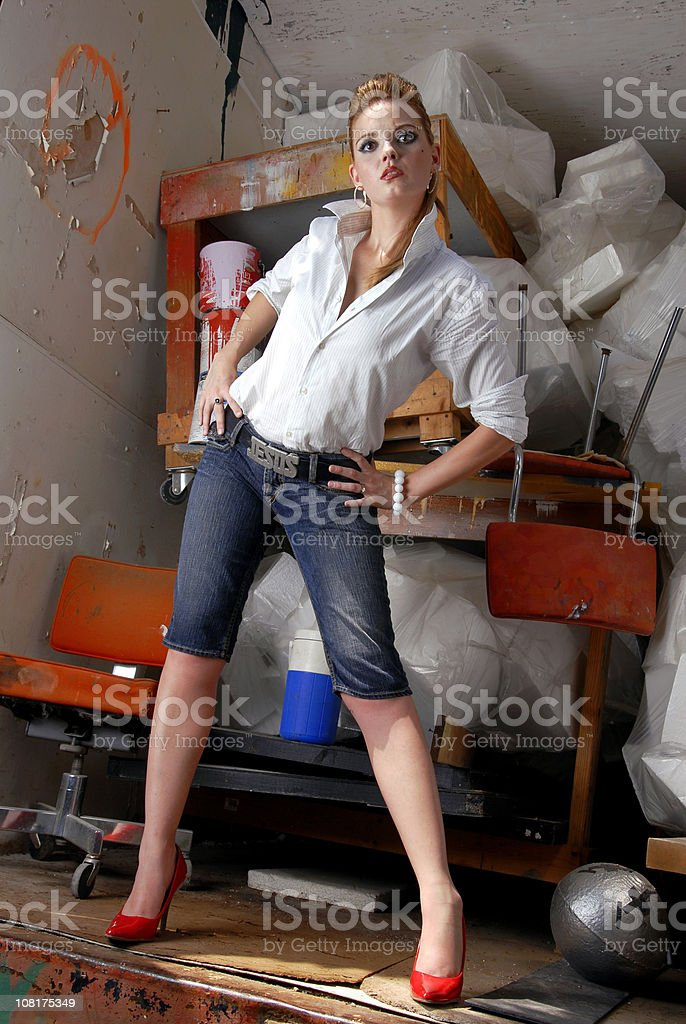 Woman Posing In Front of Garbage and Paint stock photo